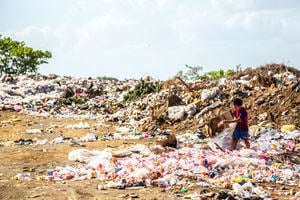 Image of a young boy looking for something to upcycle from a pile of rubbish