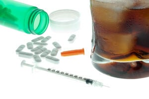 pills, a syringe and a rum and coke on a white table