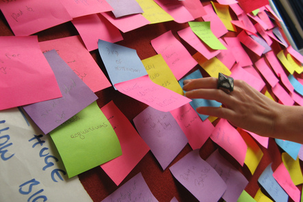 A woman adds to a wall covered in post-it-notes