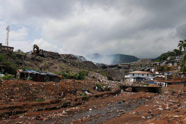 Image shows a large rubbish heap with houses on one side and smoke rising above it.