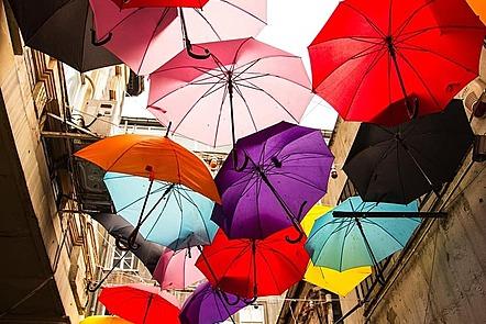 La imagen muestra paraguas de diferentes colores colgados de hilos en el exterior de una serie de edificios antiguos.