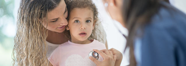 A mother holds her daughter while a doctor checks the child with a stethoscope