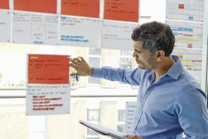 Man looking at project documentation pinned to a window, while holding a notebook.