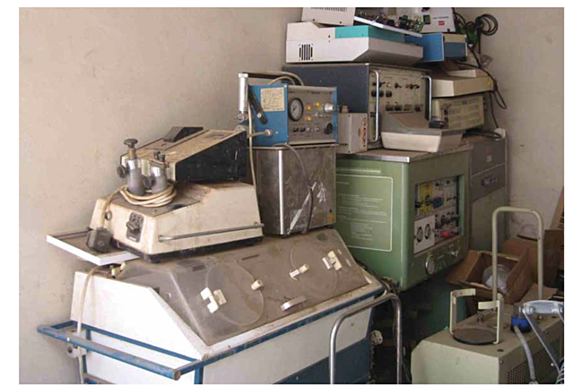 Image of equipment graveyard at West Africa hospital showing different equipment stacked on top of each other and dusty