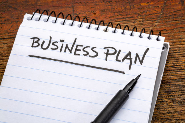 business plan - handwriting in a spiral notebooks against grunge wood
