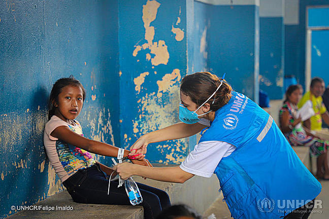 Young girl sitting on a bench inside a building with a woman wearing a mask from UNHCR putting a label around the girls wrist.