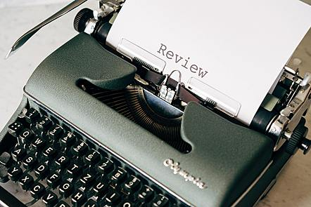 A typewriter on a table, typing a paper with Review on it