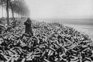 Man standing in a field of artillery shell casings during World War 1