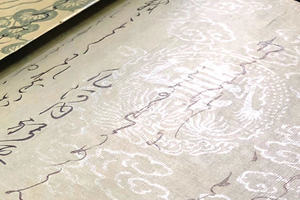 Verticaly written Japanese hand writing on a beautifully decorated white washi paper