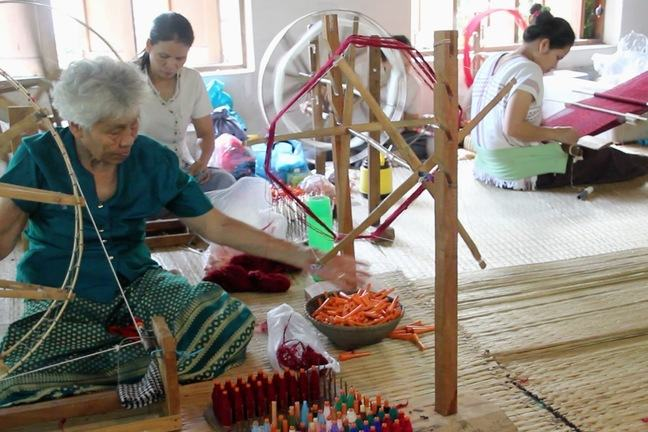 Women sitting on the floor weaving and spinning