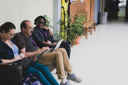 Three learners seated on a bench in a corridor, two working on their laptops and one observing.
