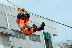 A man zip wiring down from a building during an emergency.