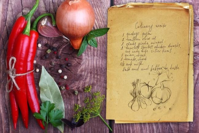 Some raw vegetables beside a handwritten recipe on a wooden table
