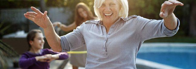 A playful image of an older woman, a teenager and young girl having fun hula hooping in a back garden next to a swimming pool.