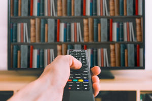TV remote pointing at TV showing a bookcase full of books