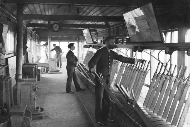 Black and white image of signalmen working in a signal box