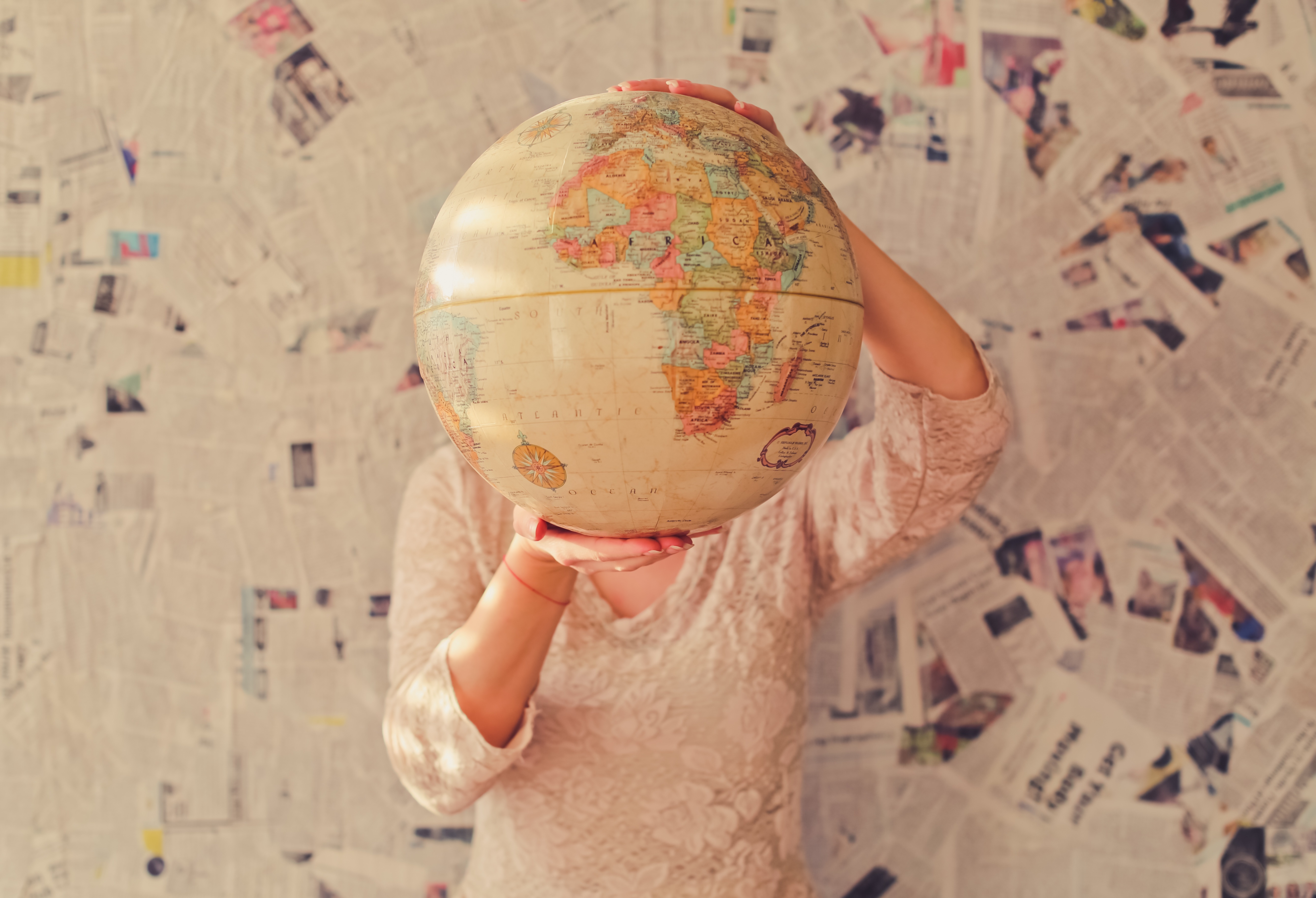 A woman holds a globe against a background of newspaper cuttings.