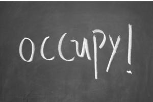 The word occupy written on chalkboard.