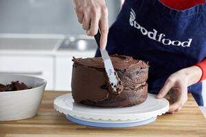 Putting icing on a chocolate cake