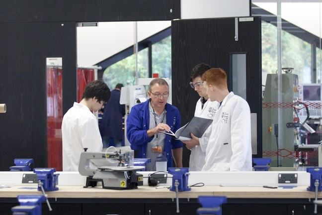 A technician advises engineering students in a workshop environment