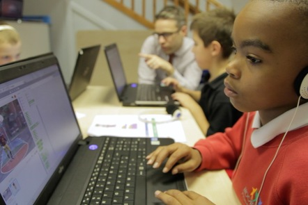 A child programming in Scratch at a laptop