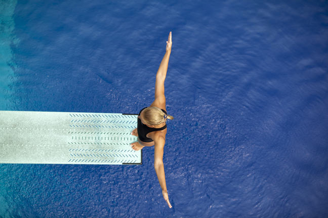 Woman standing on the edge of a diving board in a swimming pool