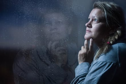 Woman thinking with reflection in window
