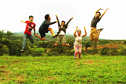 Group of five people jumping for joy