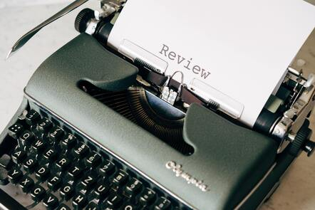 An old-fashioned typewriter with the word 'Review' typed on a piece of paper coming out of it