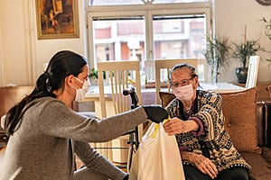 Two women wearing face masks sat down. The younger woman is handing the older woman a plastic bag