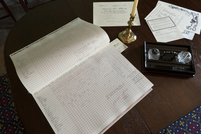 A photo of a written ledger on a wooden table