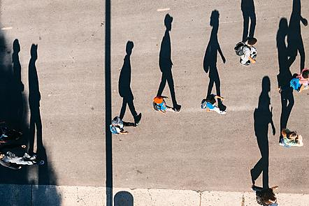 Crowd walking with elongated shadows