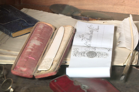 Collection of antique writing objects including glasses, magnifying glass, quill and papers