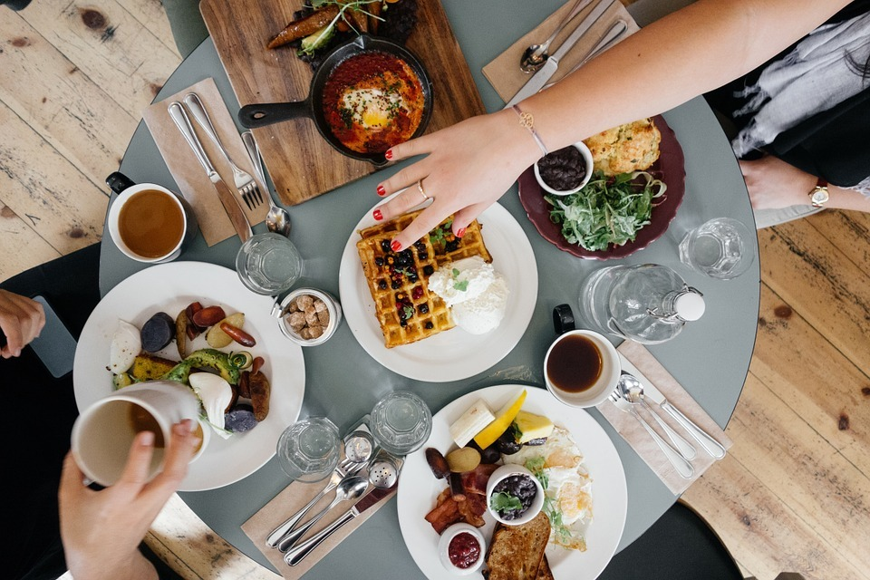 Aerial view of a round table with breakfast food on it with 2 people sitting