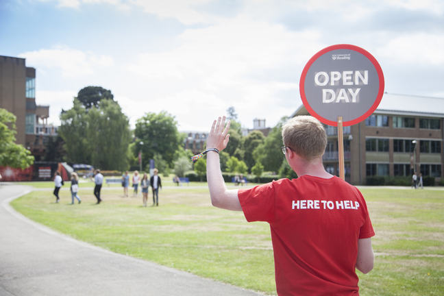 A student holding a sign saying Open Day and wearing a t-shirt with the writing here to help is ready to help prospective students during their visit.