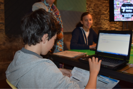 A boy coding on a laptop while referring to a handout. A girl is working on a laptop in the background.