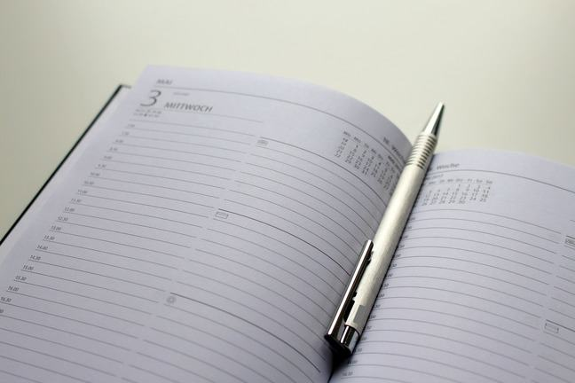 Photo of a notebook with a pen resting in the middle