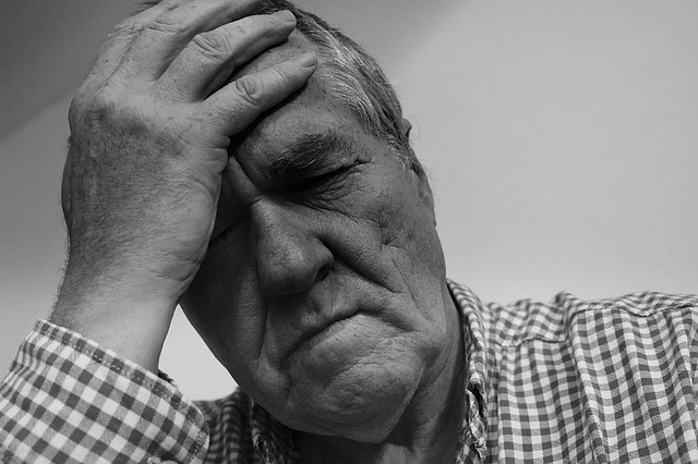Black and white image of an older gentleman resting head on right hand, eyes closed and appears in discomfort
