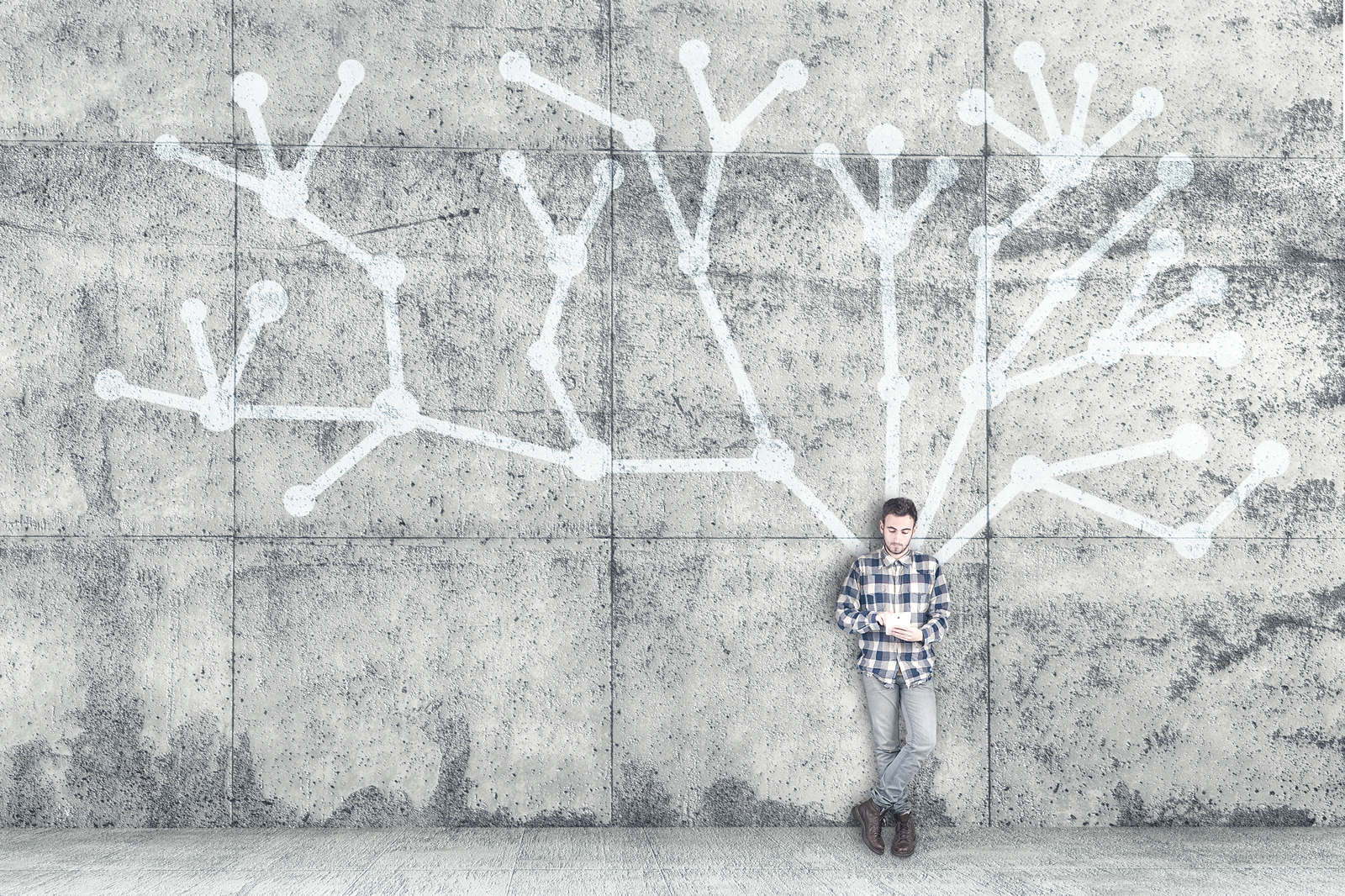 Young autistic man with tablet leaning against wall
