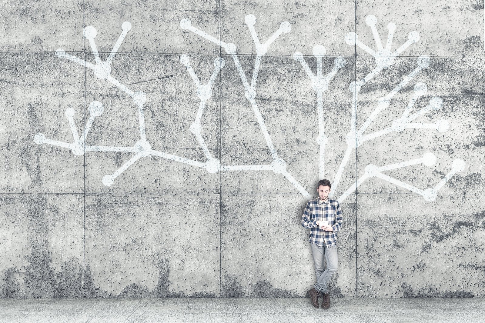 Young autistic man with tablet leaning against wall. Free online courses from University of Bath