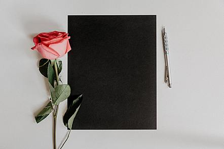 Black leather bound notebook on a table, next to a pink rose.
