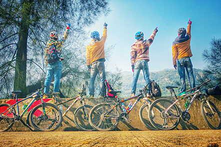 La imagen muestra 4 ciclistas en un paisaje natural. Están parados uno al lado del otro, sus espaldas hacia la cámara y apuntando con la mano derecha hacia el cielo azul. Todos están usando cascos, jeans y chaquetas. Sus bicicletas están recostadas.