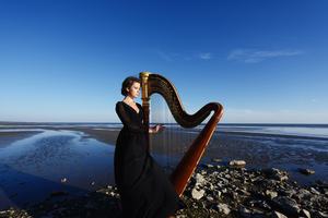 lady holding harp on Irish beach in the early evening