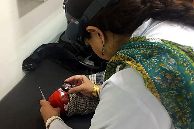 Ophtalmologist, wearing an ophthalmoscope on her head, is bent over the baby and holding a lens close to the baby's eye