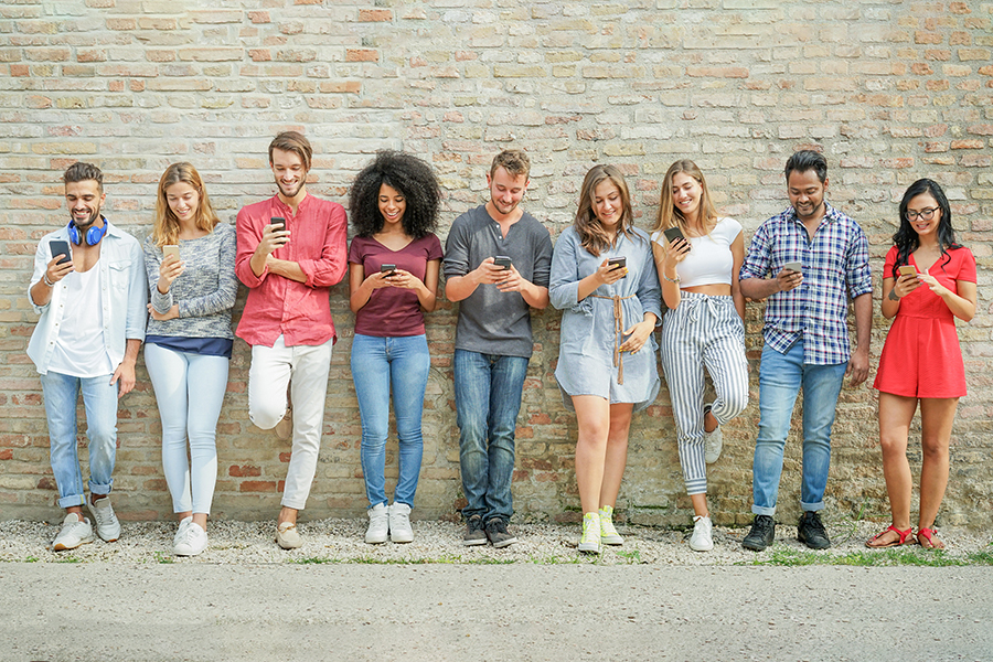 nine young adults lined up at a wall and texting
