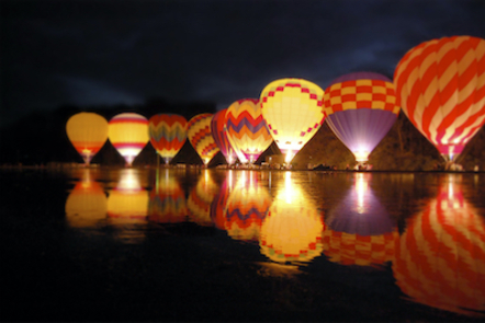 hot air balloons reflected on the surface of some water