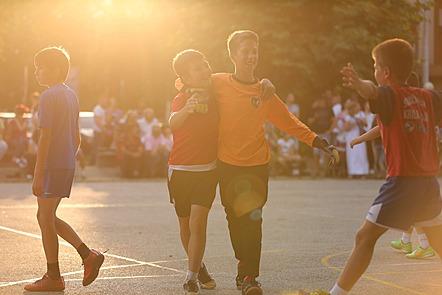 Vemos a algunos chicos en lo que parece ser un partido de fútbol. Dos de ellos se están abrazando uno al otro y otro  con sus brazos abiertos está a punto de alcanzarlos. En la parte de atrás, podemos ver a varios adultos sentados y mirando el partido.