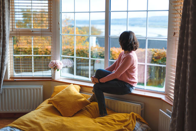 Woman sitting on a windowsill and looking out the window