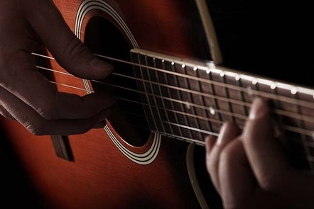 A close up image of hands playing an acoustic guitar