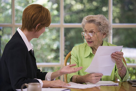 Older lady with younger professional discussing paperwork at a table